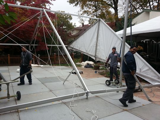 crew installing tents over flooring