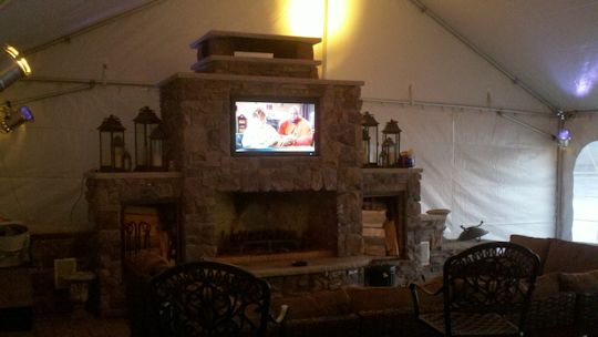 tv mounted in fire place with tent installed over construction